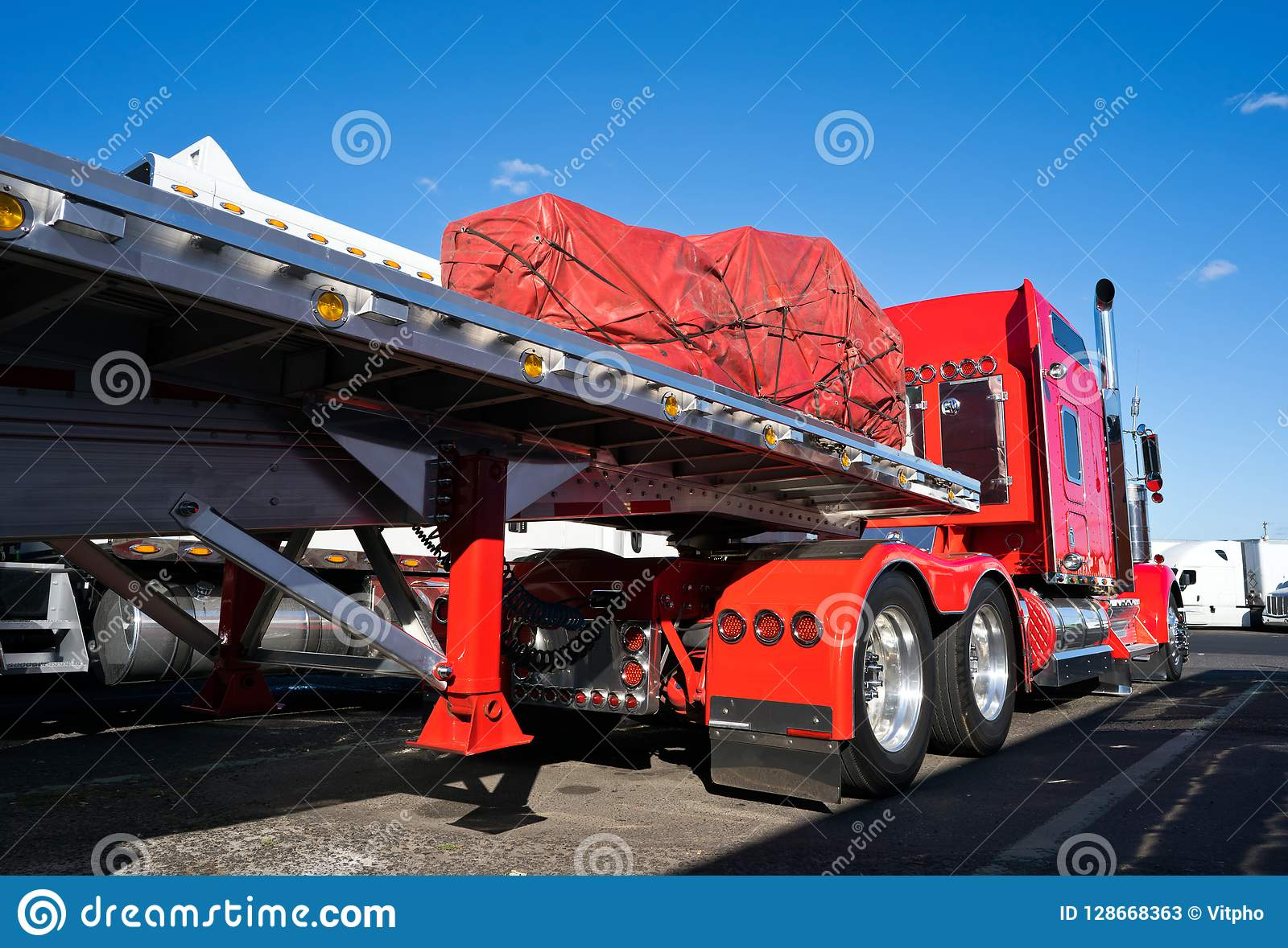 Classic Bright Red American Big Rig Semi Truck With Flat Bed Semi Trailer Standing On The Truck Stop With Covered Cargo Stock Image Image Of Delivering Fleet 128668363