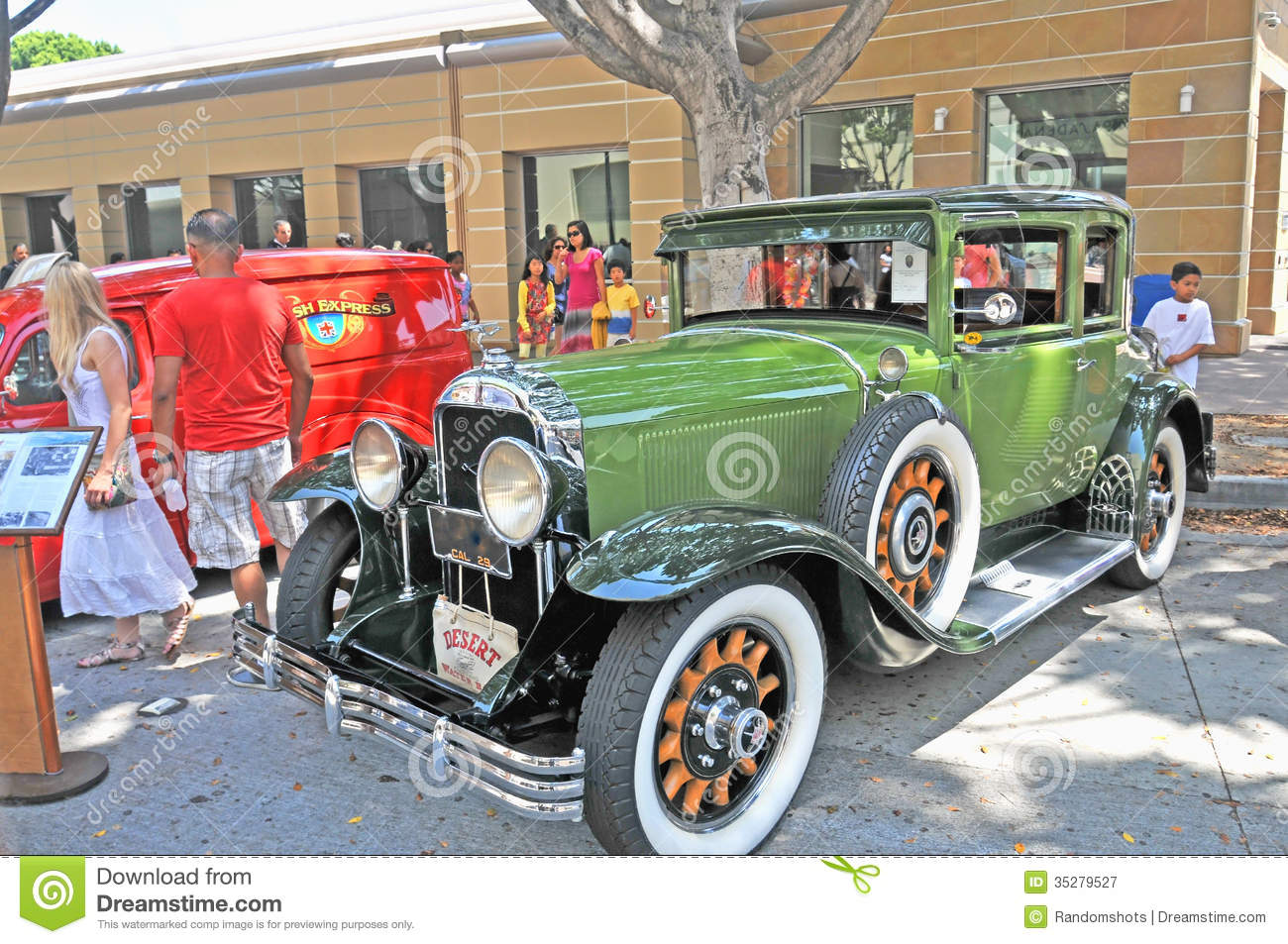 This is a beautiful olive green vintage Buick sedan from the late 1920's.  Note the fender mounted spare tire, wood spoke wheels with whitewall tires,  ...