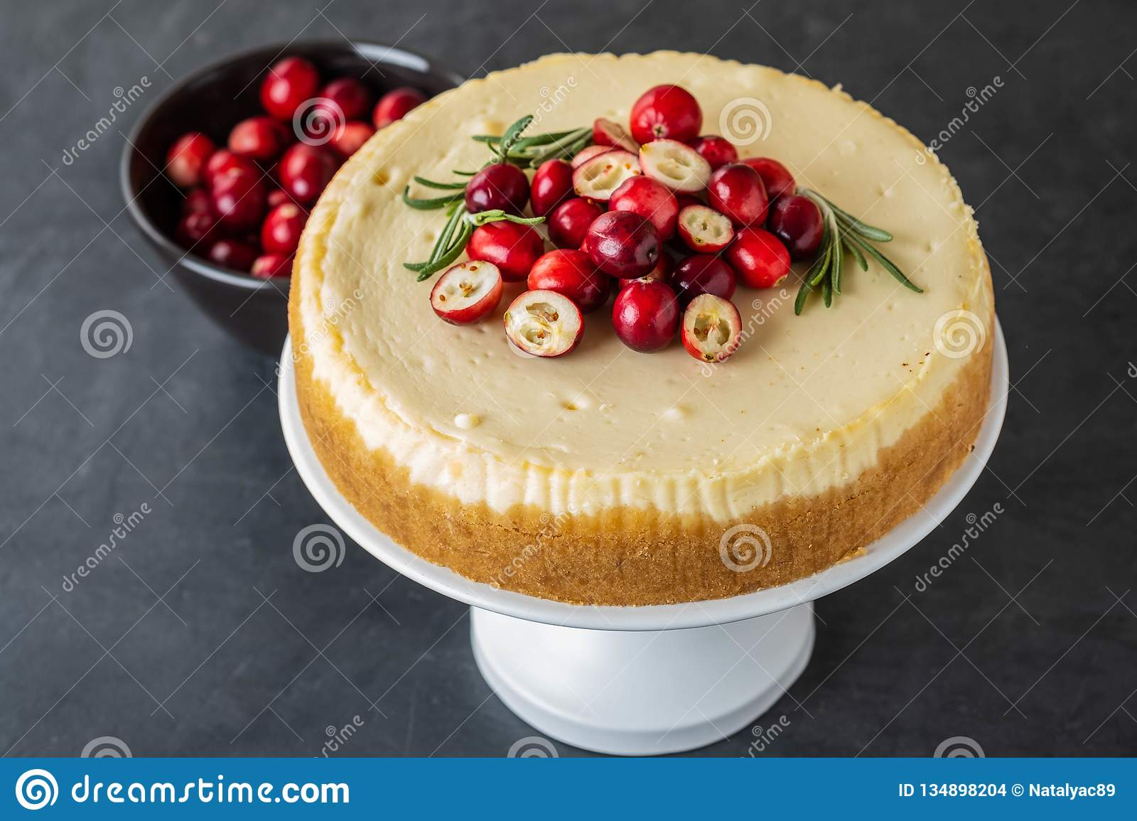 Classic cheesecake with cranberries and rosemary on a dark background. Winter version of cheesecake. Christmas