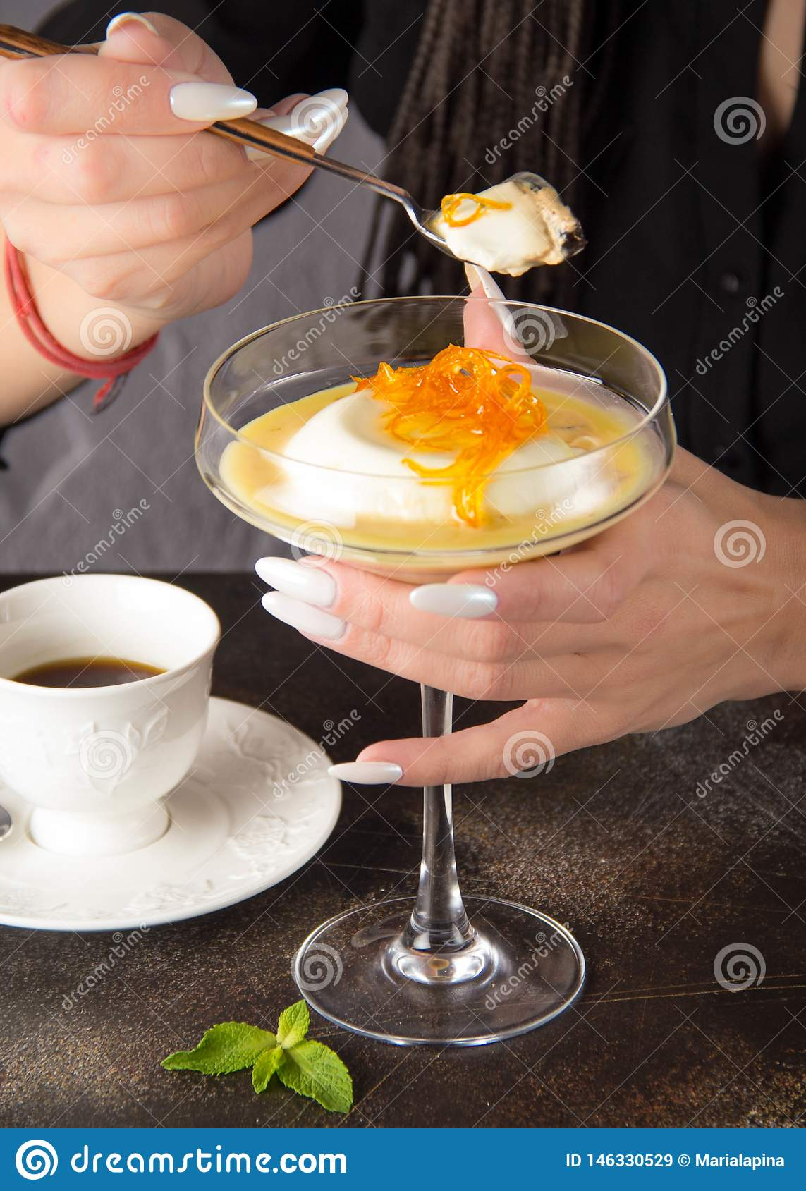 Classic dessert Panna cotta in glass with orange caramel and coffee, a woman eats with spoon