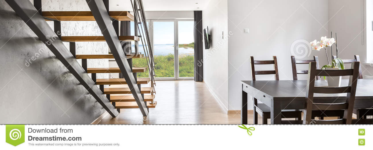 Modern And Open Interior With Classic, Dark Dining Set, Wooden Staircase  And Floor With Big Balcony Doors, Panorama
