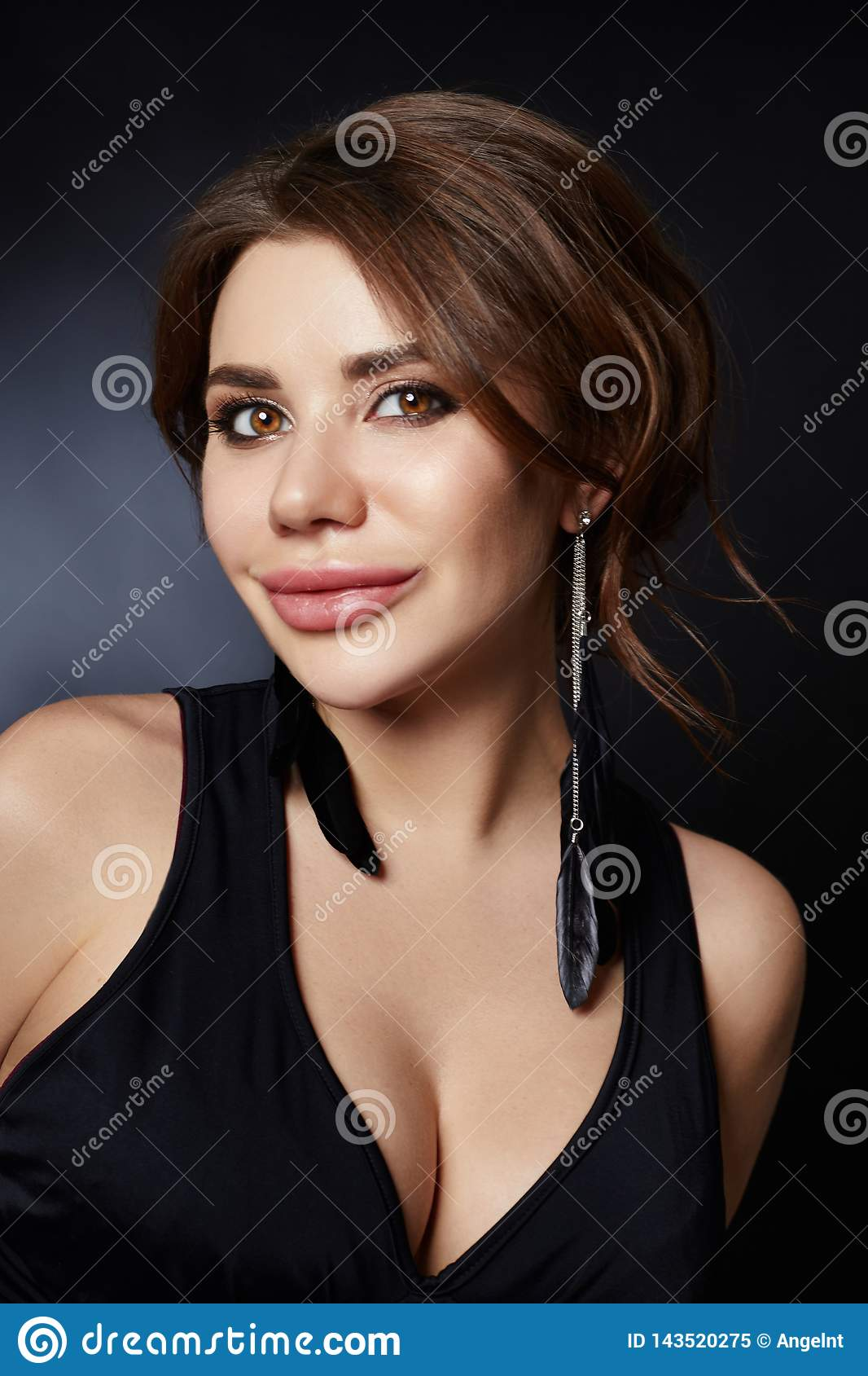 Classic portrait of a woman in a black dress on a dark background close-up. Smooth clean skin of the face girl. Large woman eyes