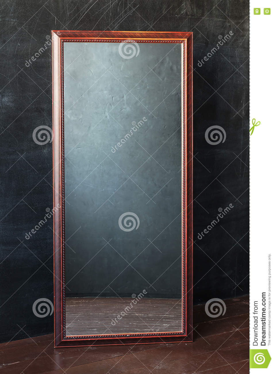 Classic rectangular mirror withot reflection standing In the empty room with black wall.