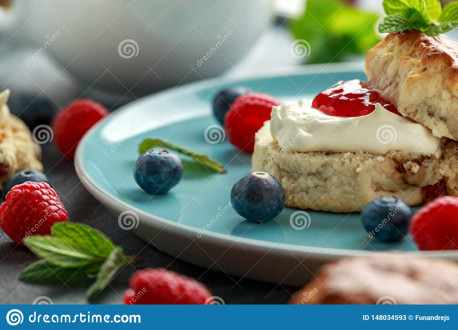 Classic scones with clotted cream, strawberries jam, english Tea and other fruit