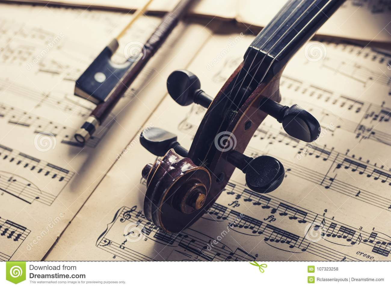 Old Antique Violin Head With Bow On Notes Stock Photo