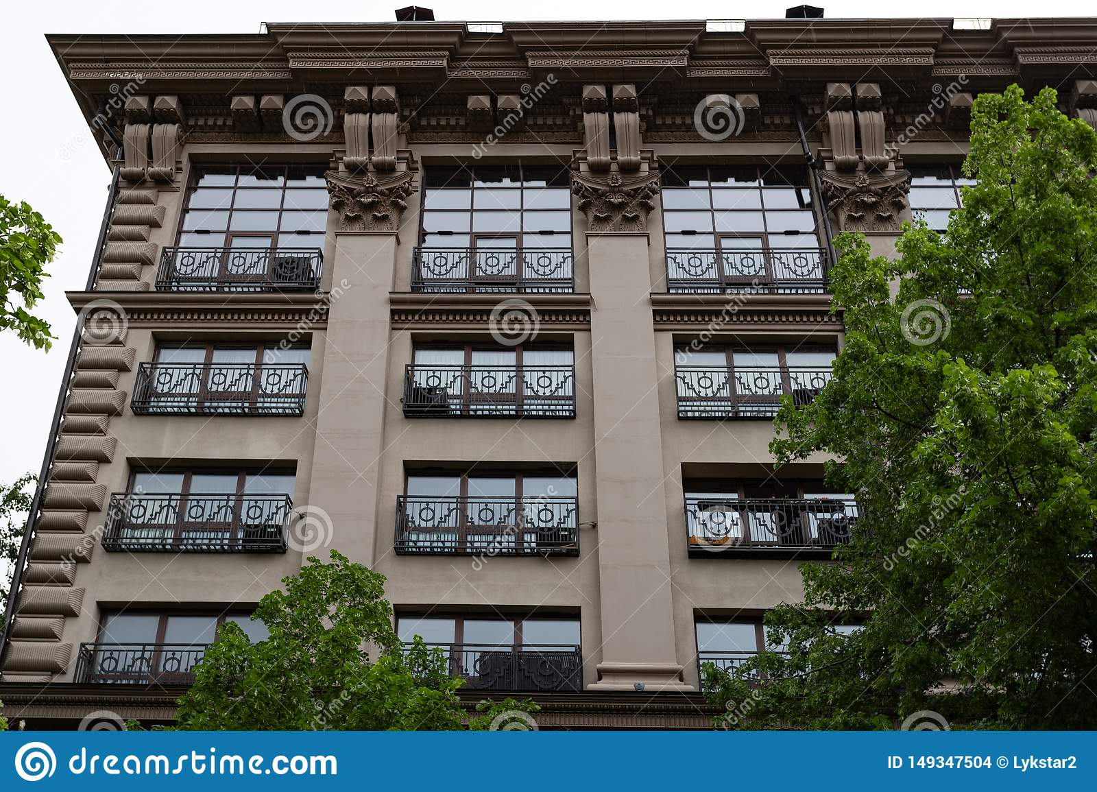 Several Windows in a row on the facade of the old building. Windows in a row on a marble wall. Rows of Windows on a tall building