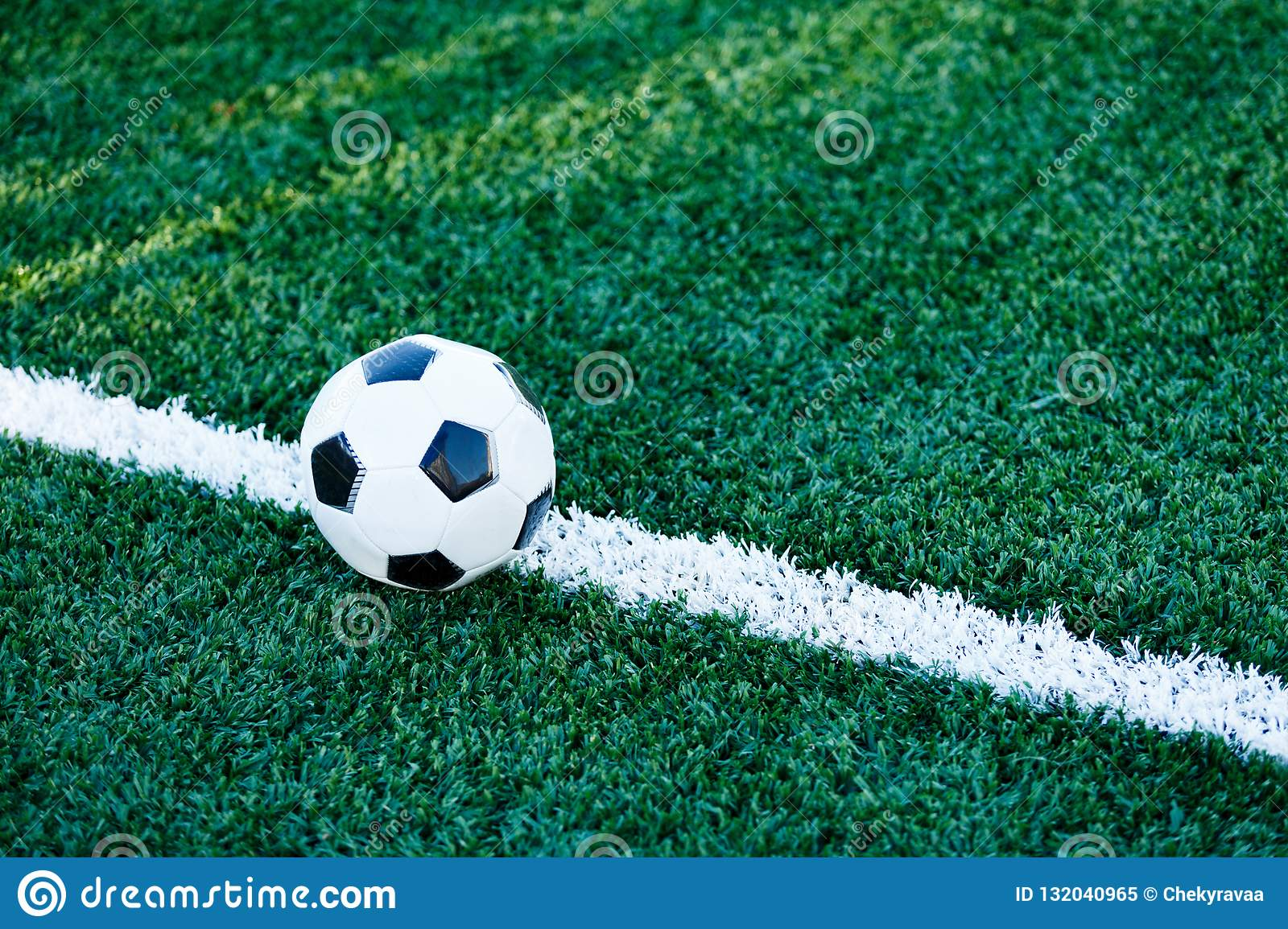 Classical black and white football ball on the green grass of the field. Soccer game, training, hobby concept.