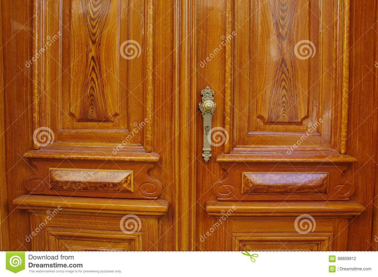 Classical wooden entrance double doors with golden antique door handle and keyhole