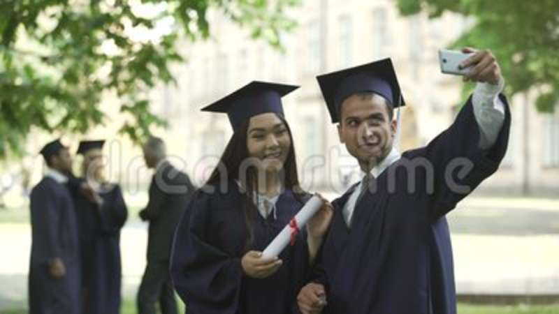 bf17f4c5a8f Classmates In Graduation Outfit Taking Selfie