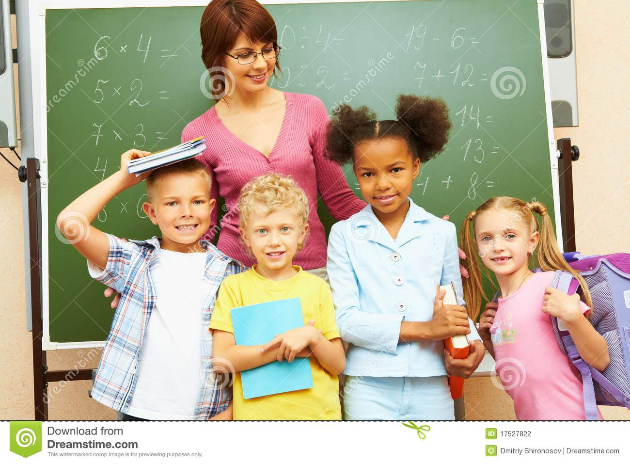 ... of several kids and their teacher standing by blackboard in classroom