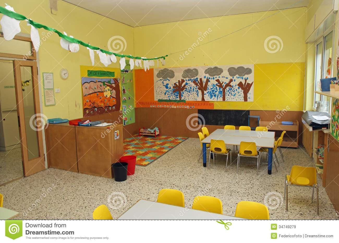 Classroom In A Kindergarten With Tables And Yellow Chairs