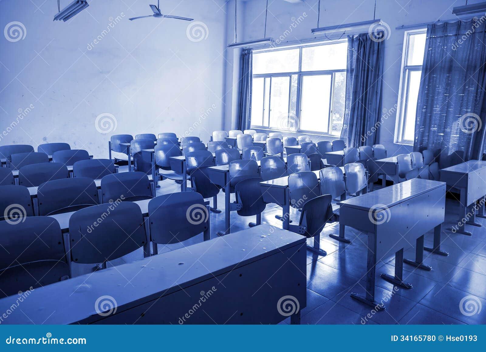 neat rows of school desks in classroom with blue tones