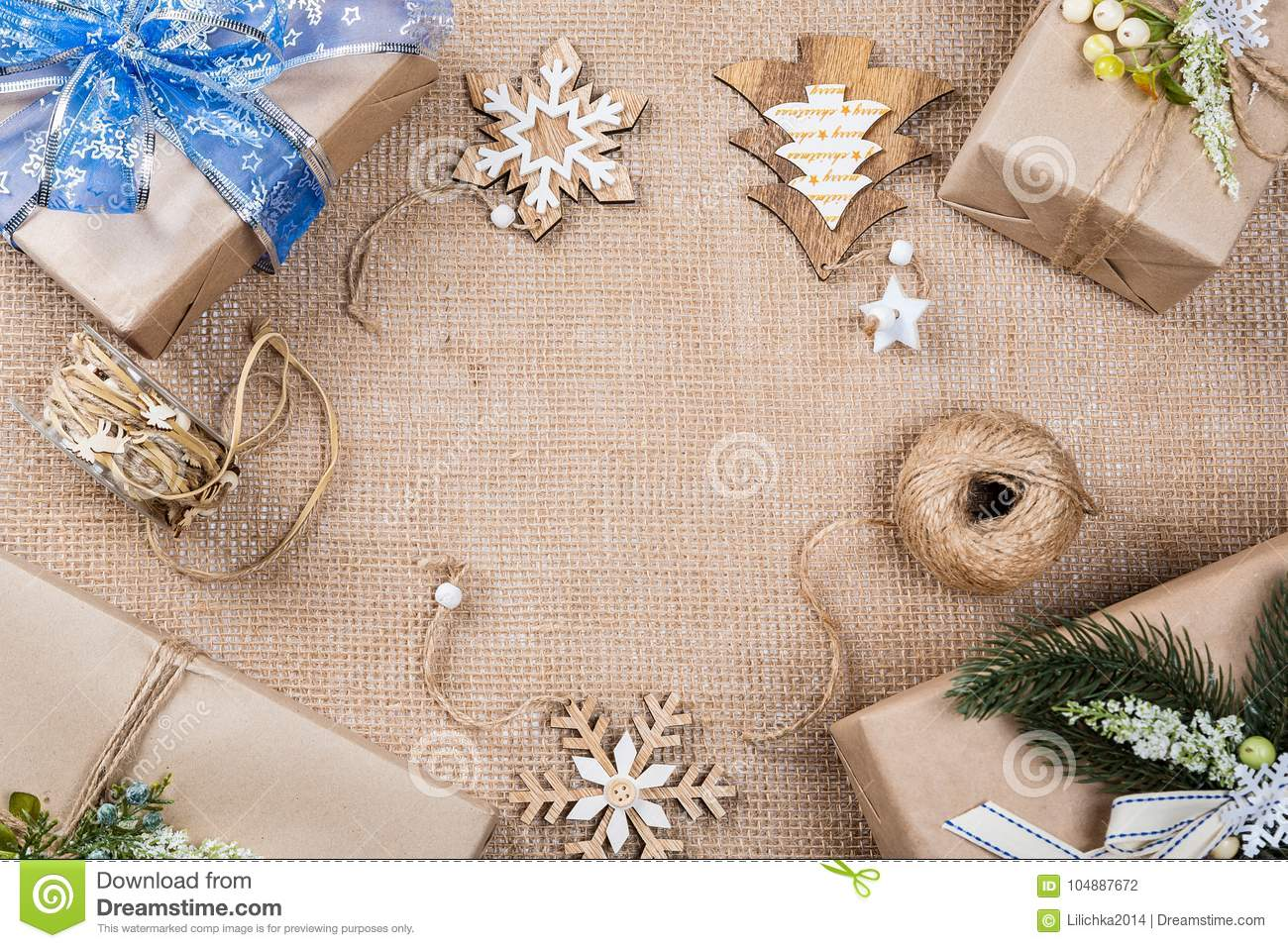 classy christmas gifts box presents in brown paper with toys and new year decor on burlap