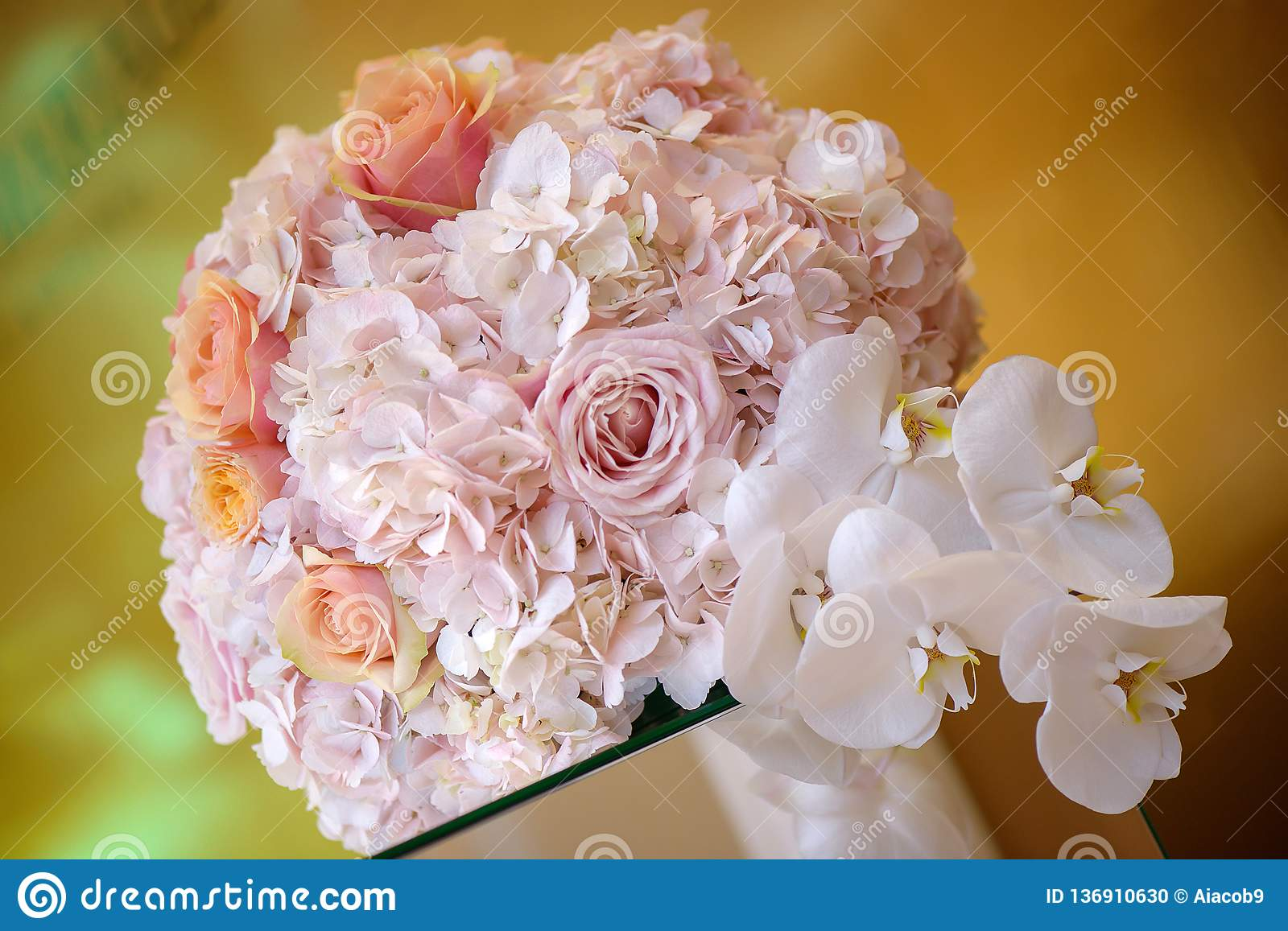Classy floral arrangement in a pastel round bouquet featuring pink hydrangea roses and orchids