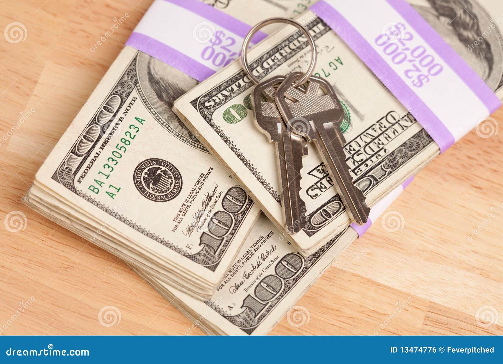Claves de la casa en la pila de dinero