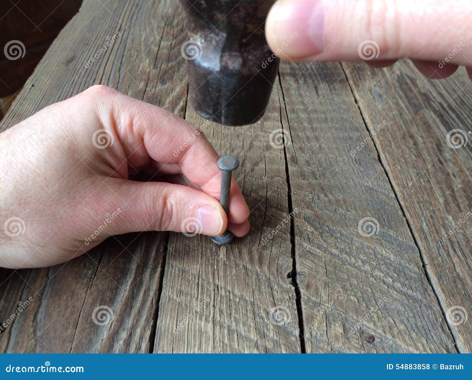 Clavo y martillo en una mano