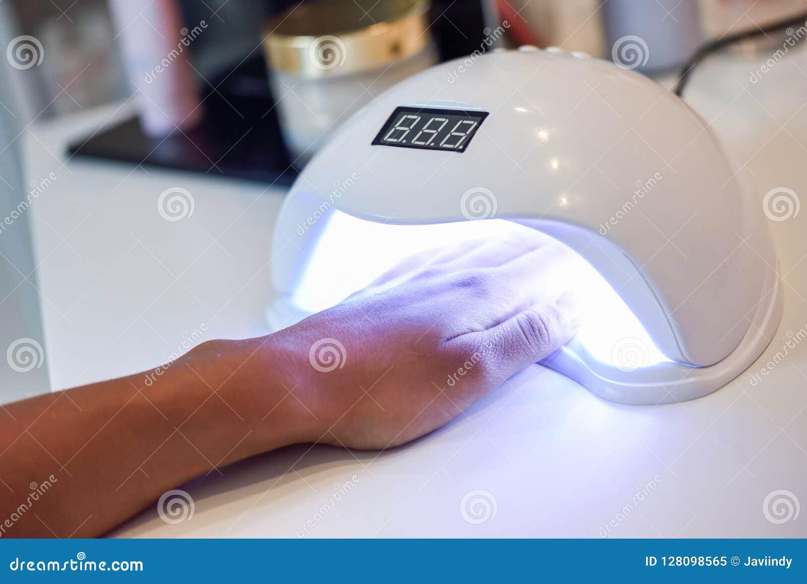 Clavos Manicured en lámpara ULTRAVIOLETA en salón de belleza