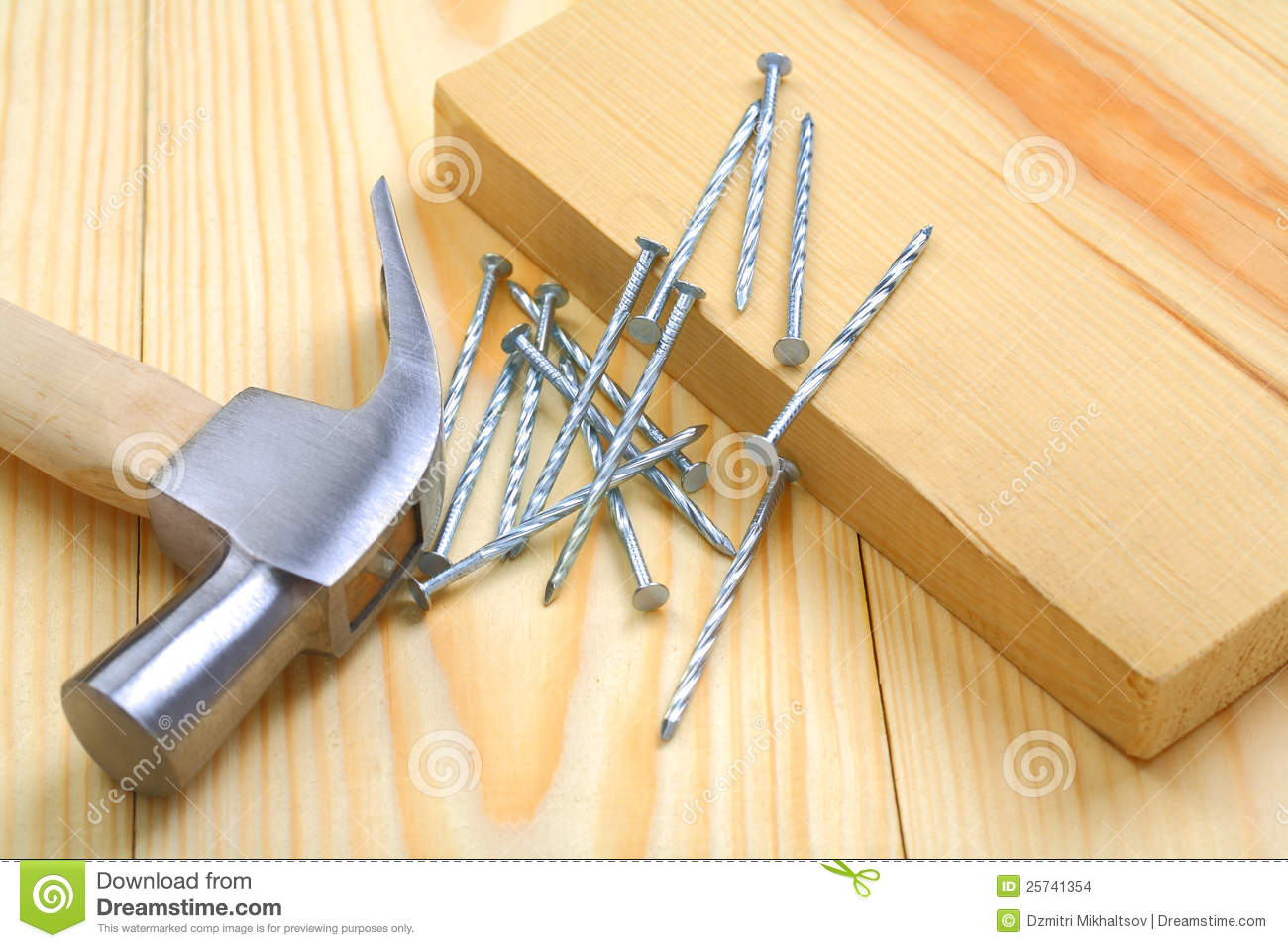 Claw hammer with nails and timber on table