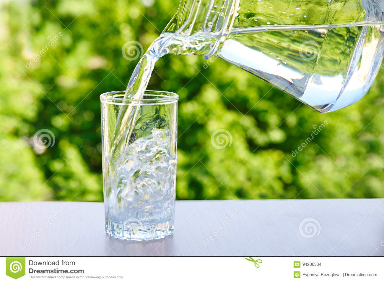 Clean drinking water is poured from a jug into a glass