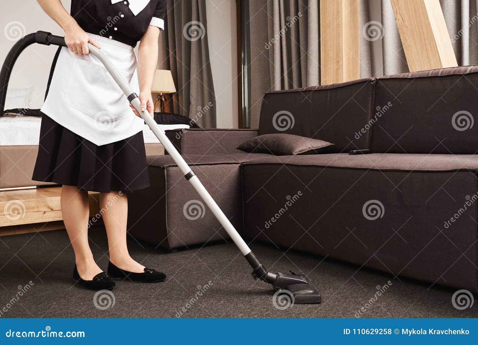 Clean house è chiave per produttività Colpo potato della cameriera durante il lavoro, salone di pulizia con l aspirapolvere