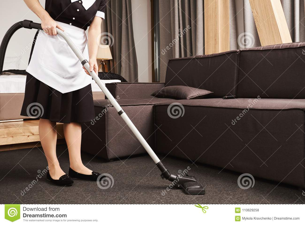 Clean house is key for productivity. Cropped shot of housemaid during work, cleaning living room with vacuum cleaner
