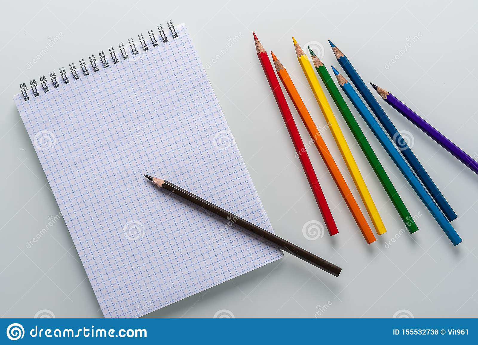 Clean notepad in a cage with a pencil lying on it and rainbow color pencils on a white background top view copy space