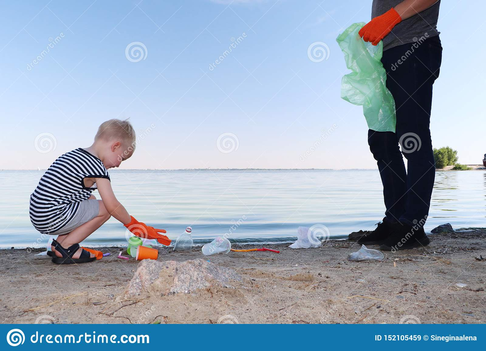 A small child collects trash on the beach. His dad points his finger where to throw garbage. Parents teach children cleanliness.