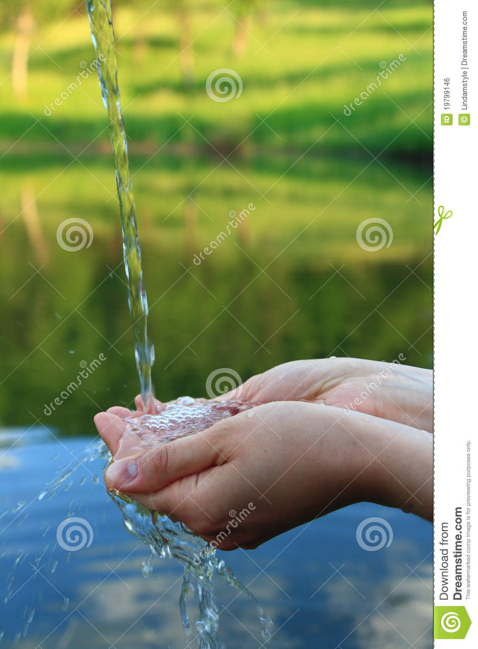 Hands in clear water against mountain lake