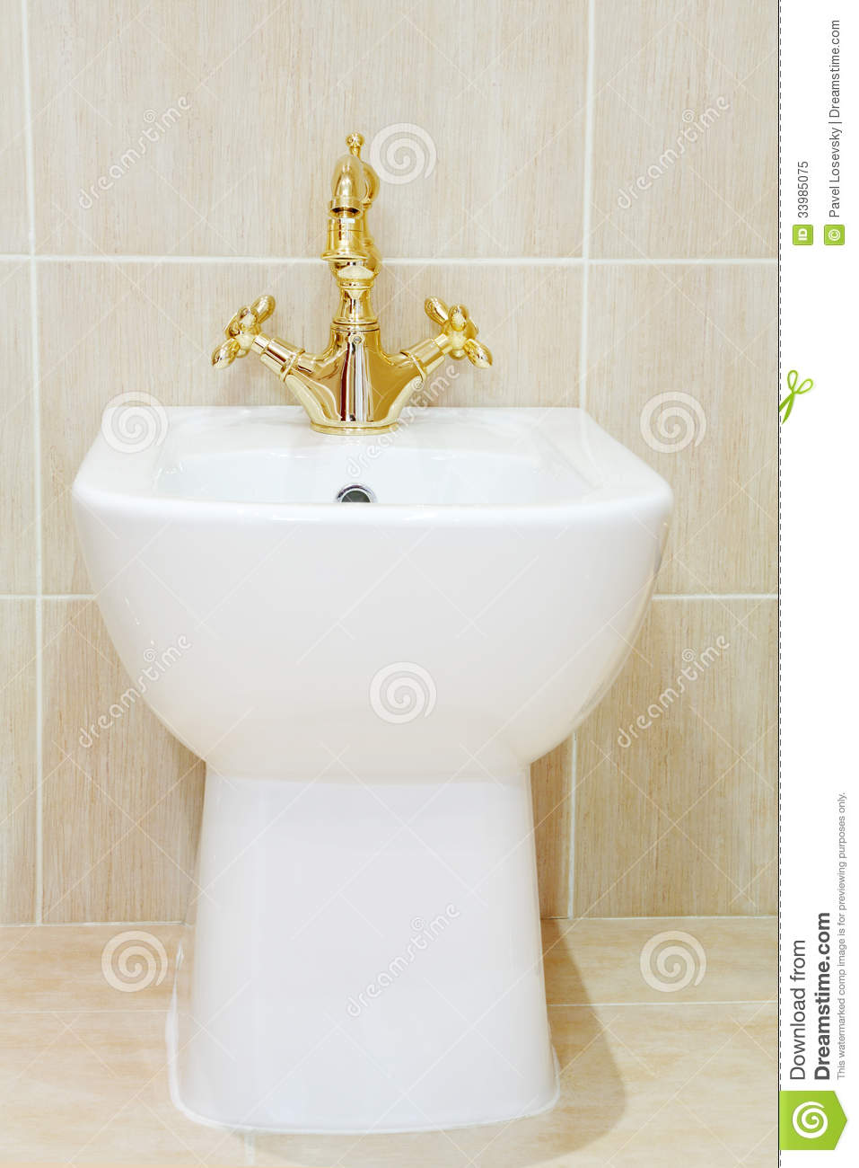 Clean And White Bidet With Gold plated Faucet Royalty Free