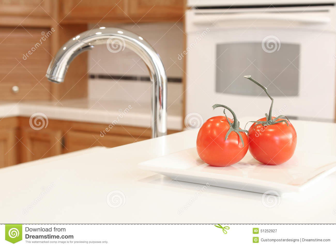 A clean white kitchen with two red tomatoes.