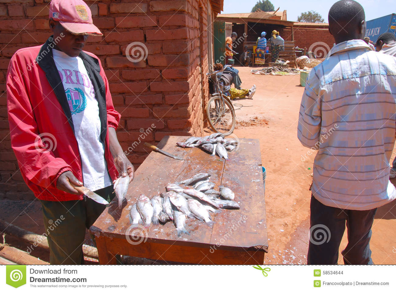 Cleaner of fish at the market of pomerini in tanzania for Village fish market