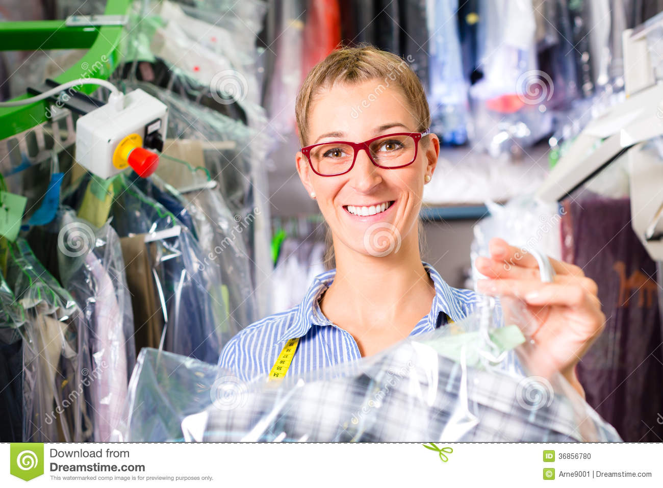 Cleaner in laundry shop checking clean clothes
