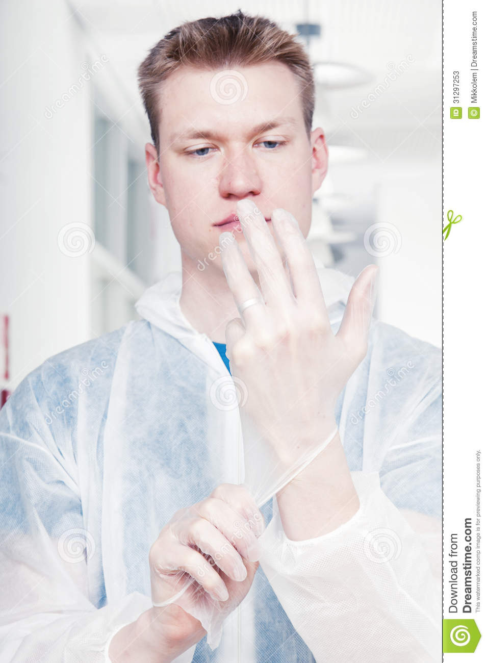 Man cleaning office wearing protective overalls, putting rubber gloves ...