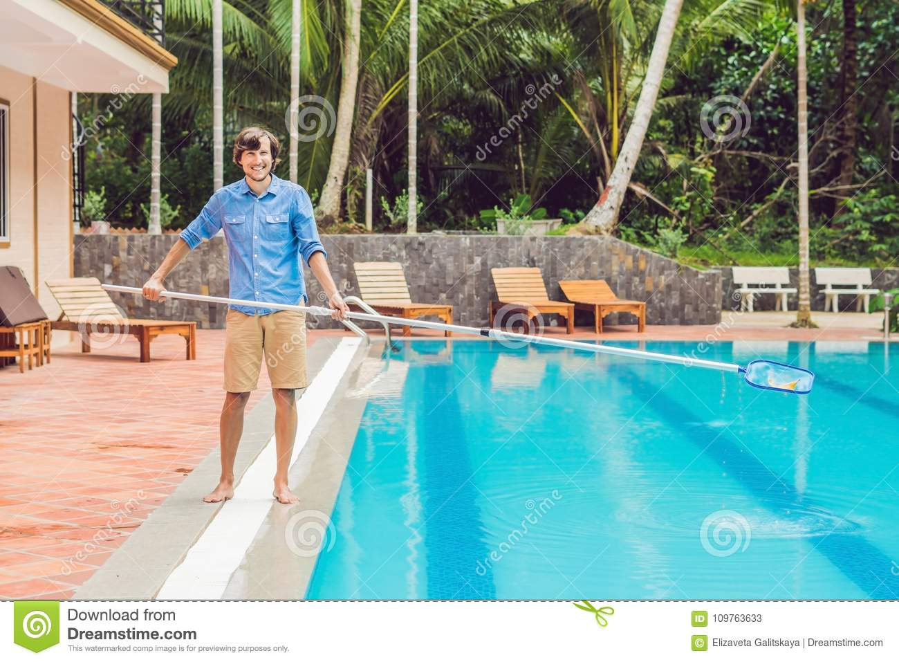 Cleaner Of The Swimming Pool Man In A Blue Shirt With Cleaning Equipment For Swimming Pools