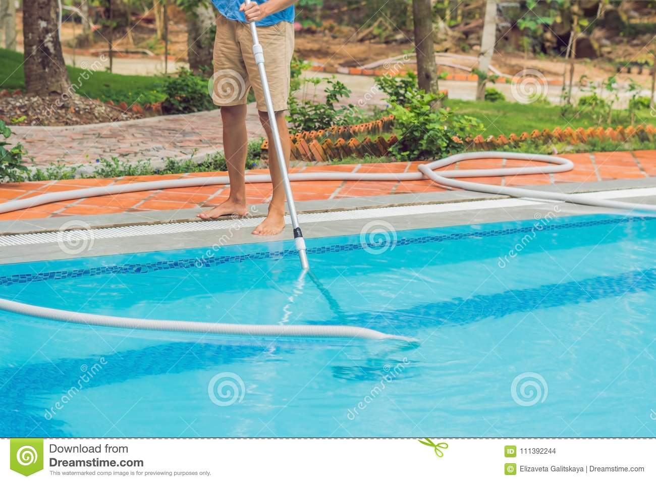 Cleaner Of The Swimming Pool . Man In A Blue Shirt With ...