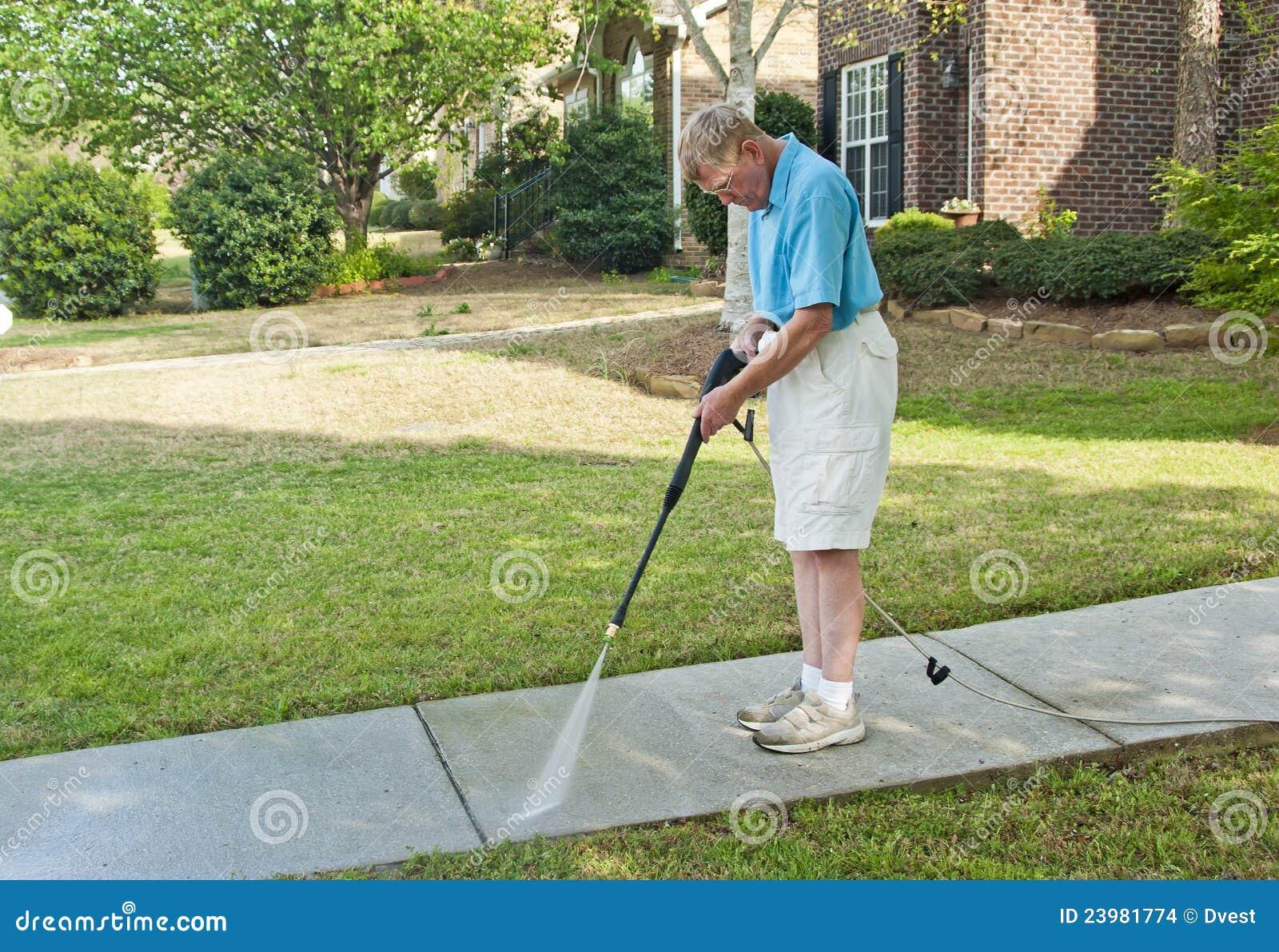 Male Pressure Washing Sidewalk Royalty Free Stock Photo