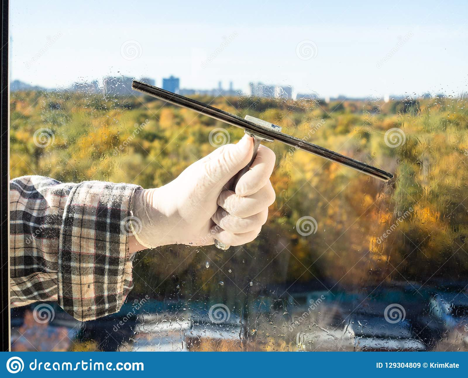 cleaning a home window glass by squeegee