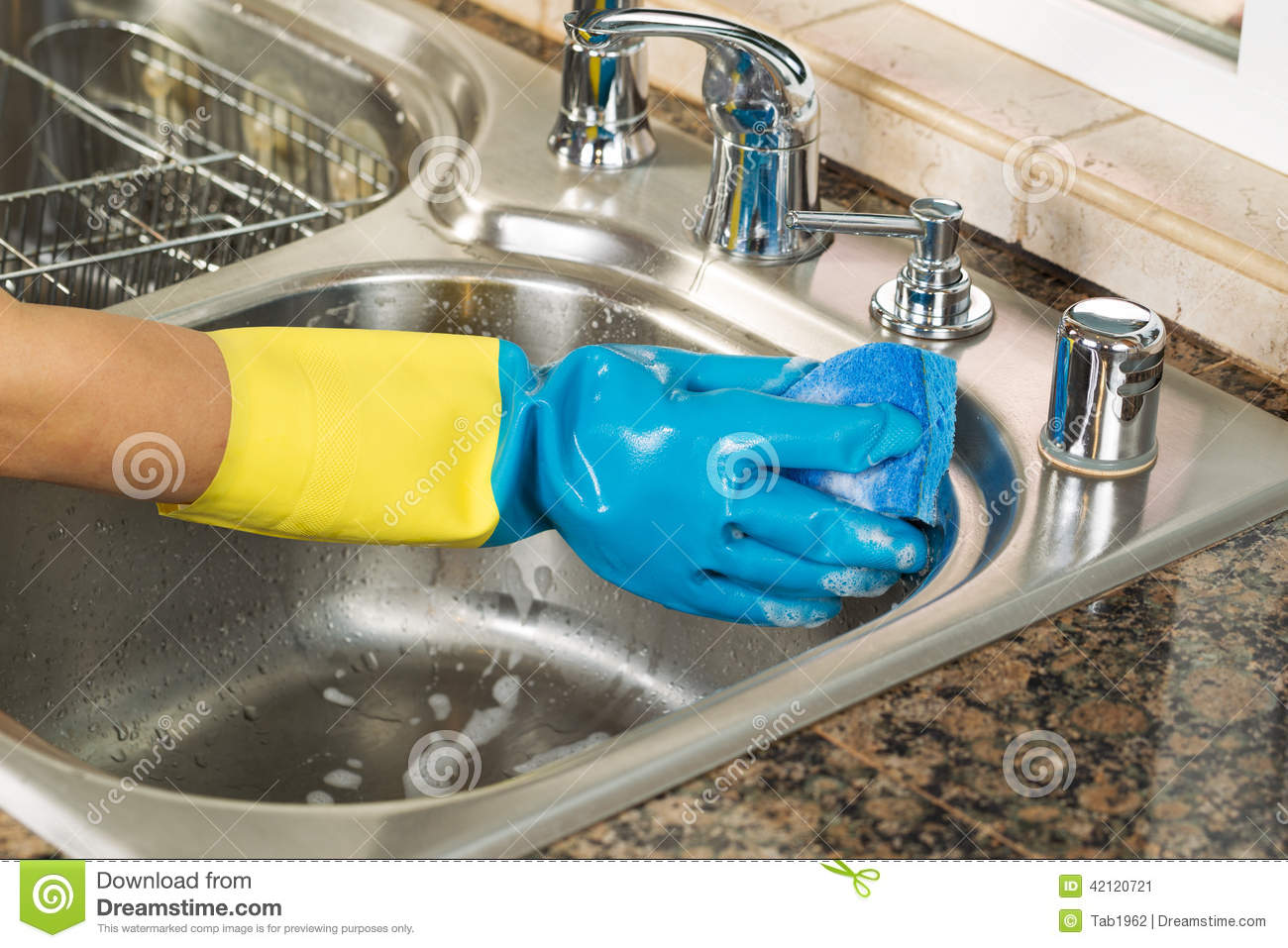 Cleaning inside of kitchen sink with soapy water and sponge