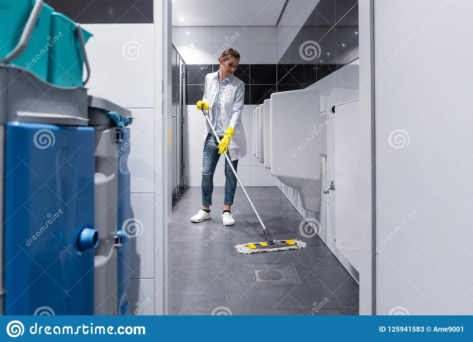 Cleaning lady mopping the floor in mens restroom