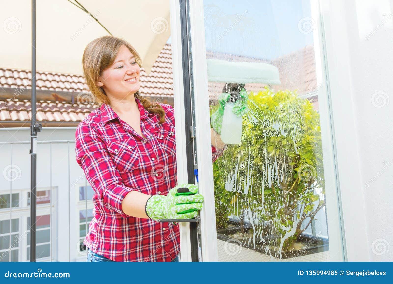 Cleaning pojęcia dishwashing ciecza gąbki Młodej kobiety płuczkowy okno, zakończenie w górę