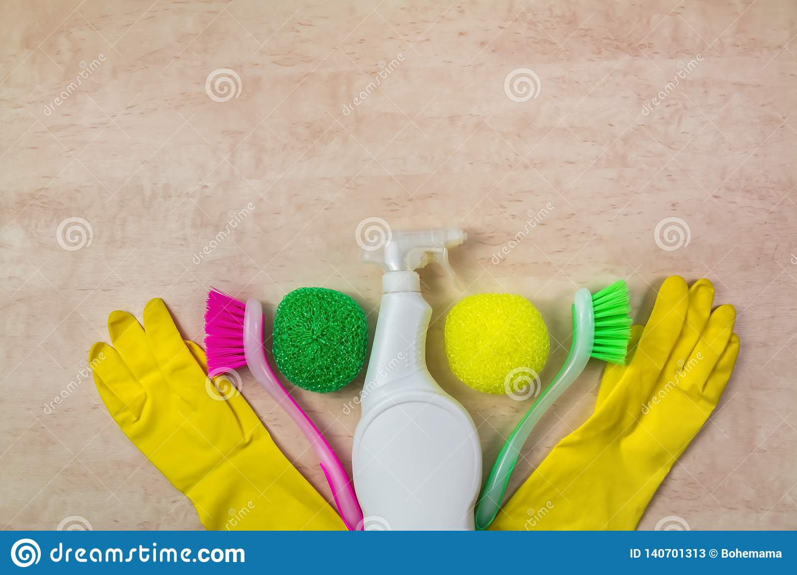 Cleaning supplies and products on wooden background, housework concept, top view with copy space