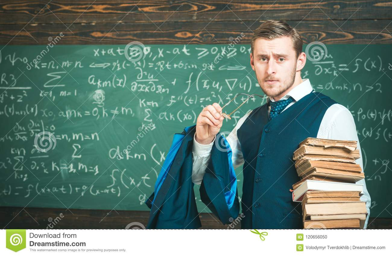 Clear explanation. Teacher formal wear and glasses looks smart, chalkboard background. Man in end of lesson takes off