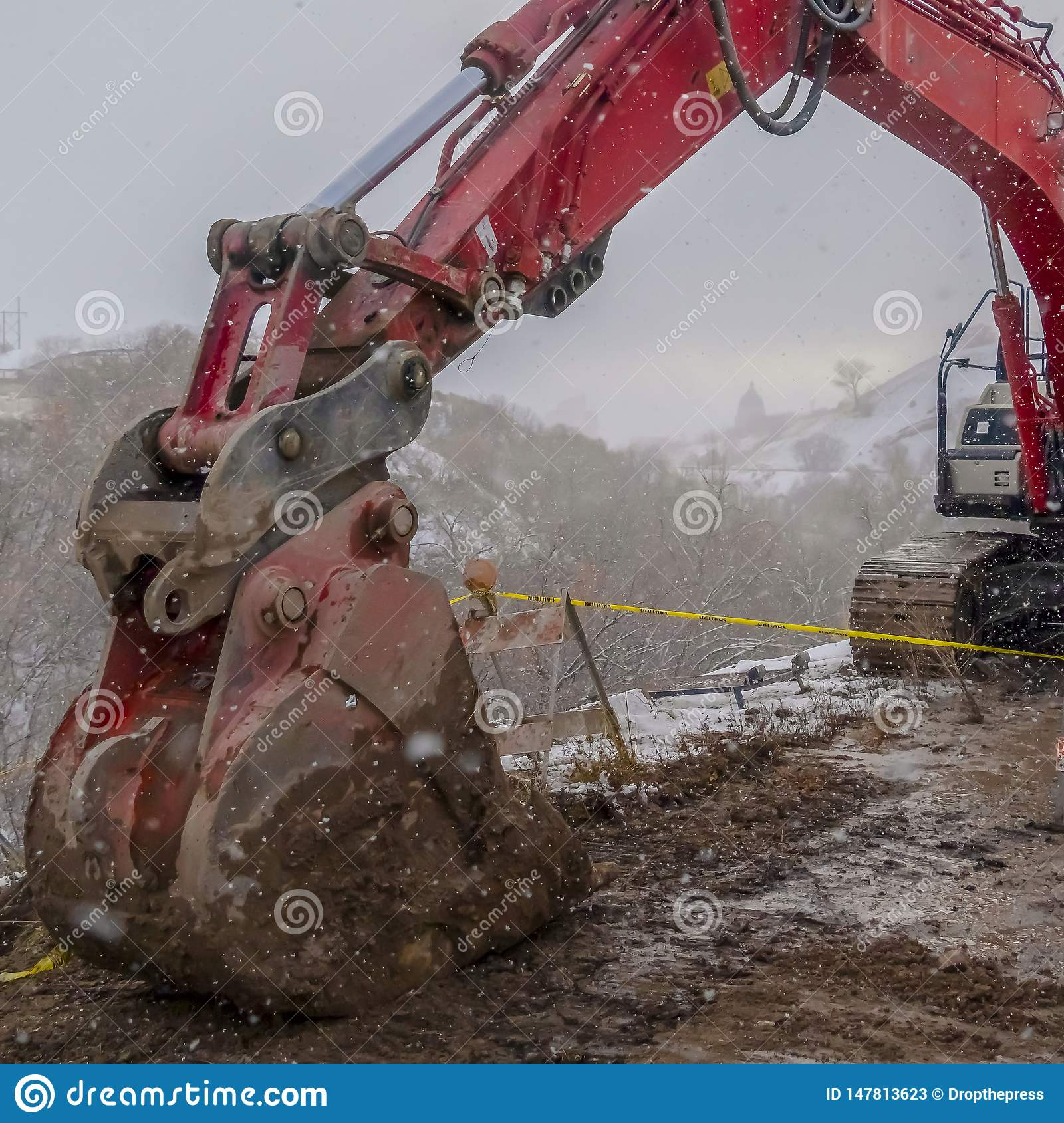 Clear Square Red excavator and barricade on a muddy mountain road viewed in winter