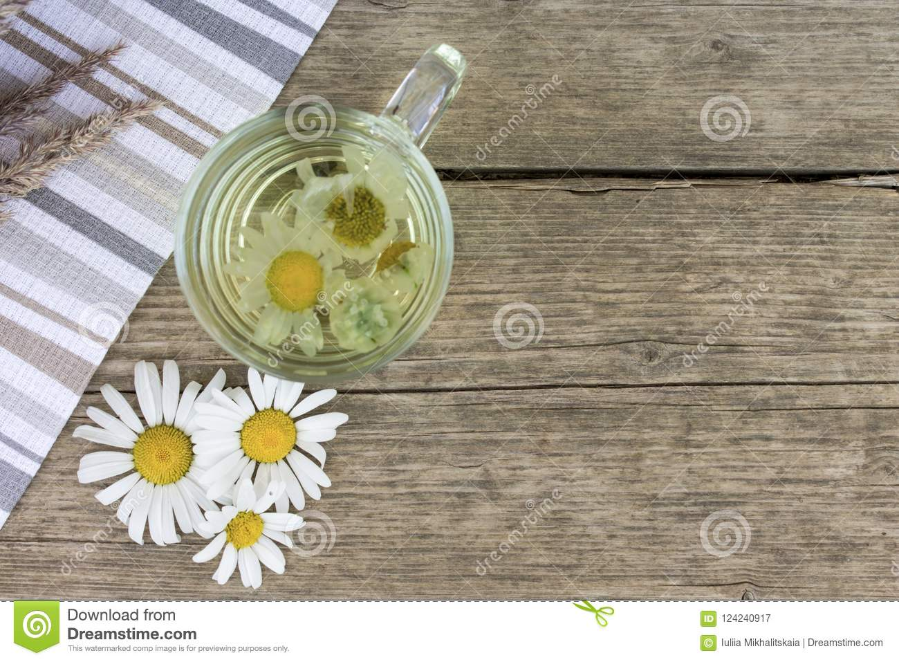Clear transparent cup of camomile tea on vintage wooden background with dried herbs, daisy flowers and copy space.