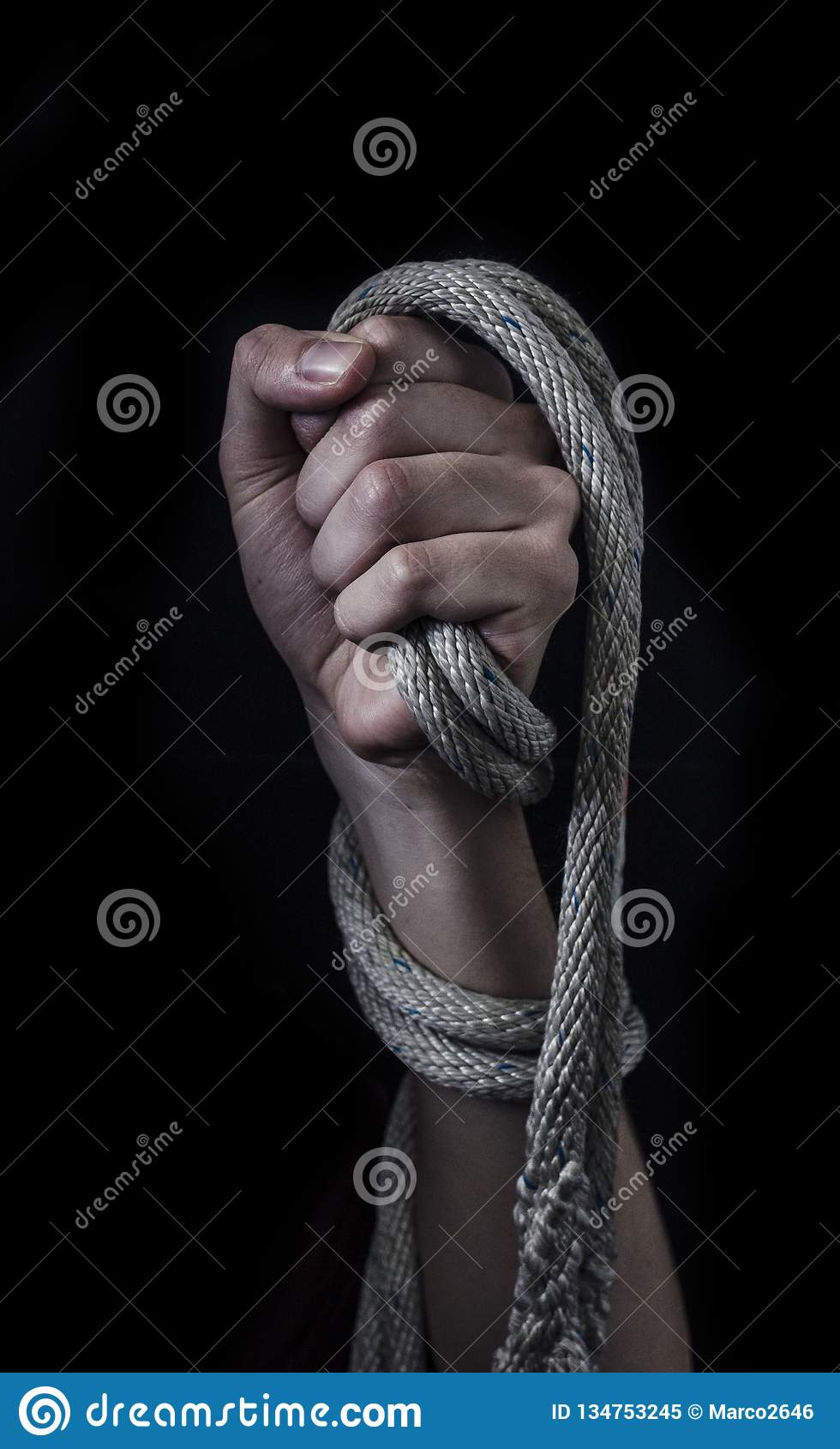 Clenched fist with tied up with a rope.