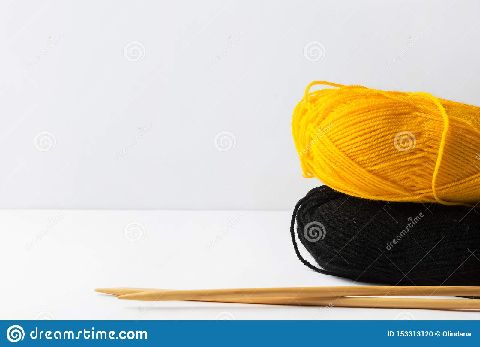 Clews of yellow black fine wool yarn wooden knitting needles on white table on wall background warm autumn color palette. Crafts