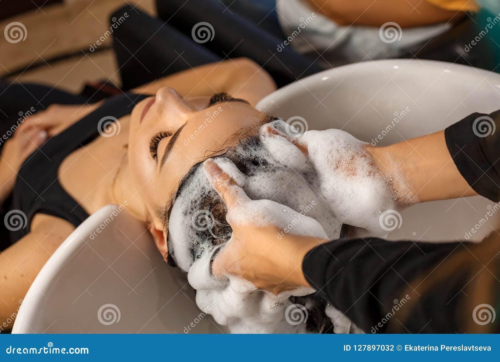 Client heureux dans un salon de coiffure qui se lavent les cheveux avec le shampooing