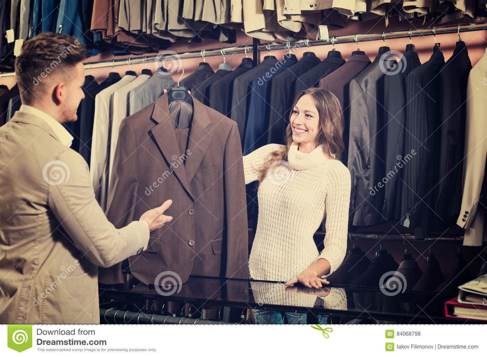 Cliente de ajuda fêmea do assistente de loja para escolher o terno