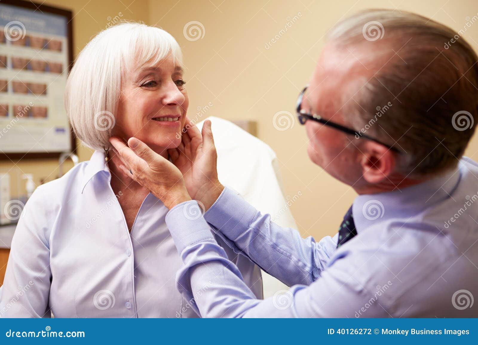 Cliente de Examining Senior Female do cirurgião cosmético dentro