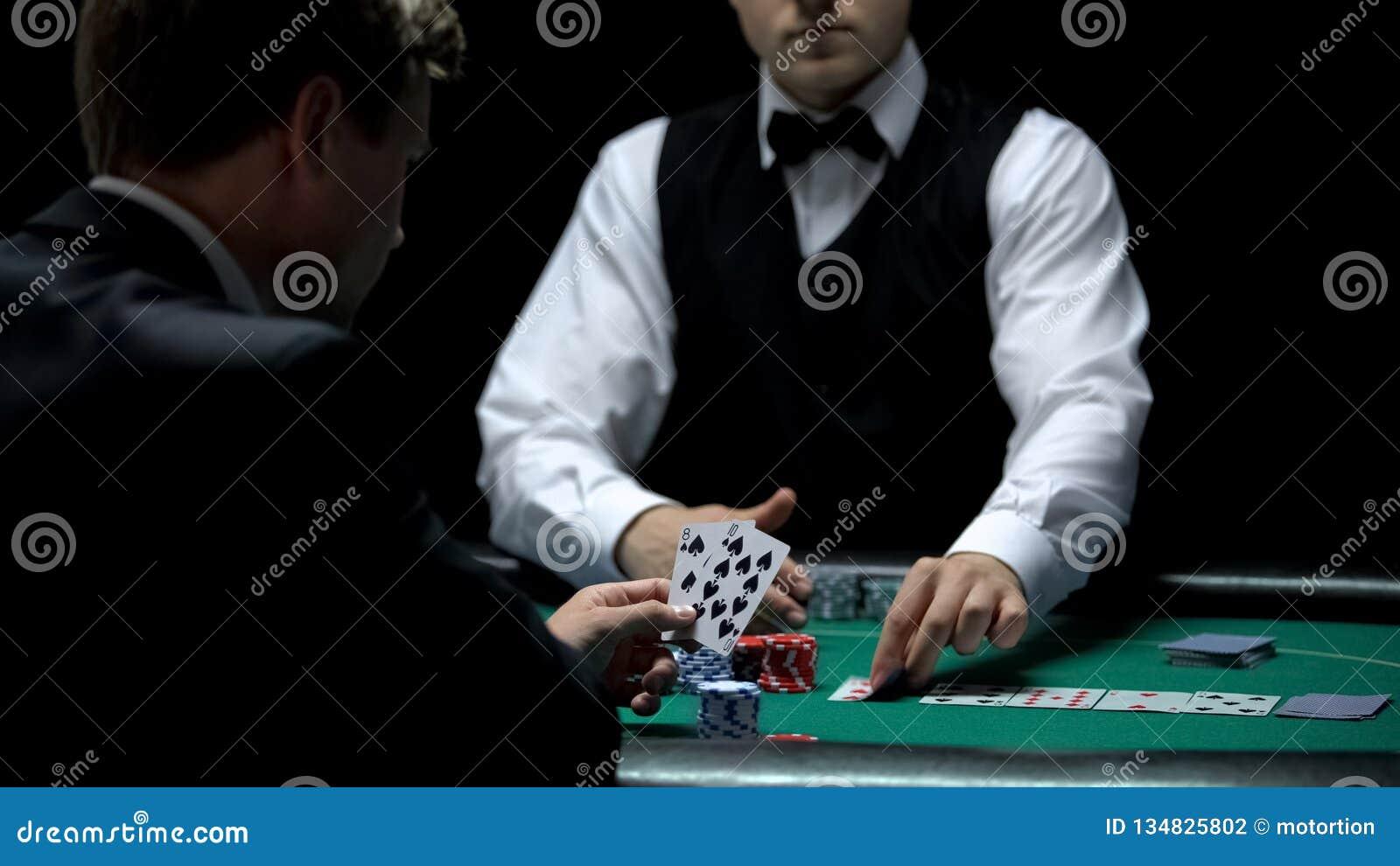 Cliente do casino da virada que tem a combinação má no pôquer, vitórias fracas dos cartões da casa da mão